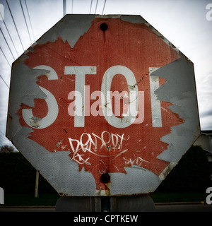 Cierre de viejos, peeling stop-signo en pésimas condiciones, con graffiti. Imagen De Stock