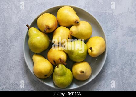 Verde y amarillo de las peras en un recipiente. Imagen De Stock