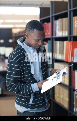 Macho negro de 19 años, estudiante de la Universidad investiga los artículos en la biblioteca escolar. Imagen De Stock