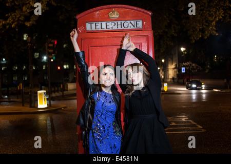 Dos amigas jóvenes bailando en la parte delantera de la caja del teléfono rojo por la noche, Londres, Imagen De Stock