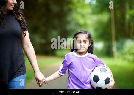 Retrato chica con pelota de fútbol con las manos de la madre Imagen De Stock