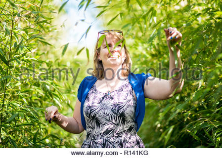 Vista frontal de una sonriente joven mujer de pie contra plantas Imagen De Stock
