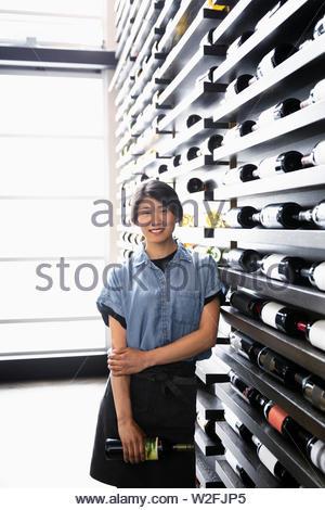 Retrato sonriente, seguros de sommelier de pie al estante de vino en el restaurante Imagen De Stock