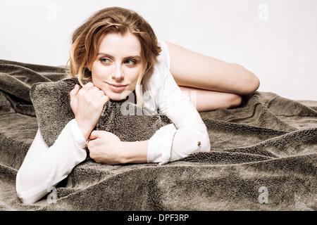 Mujer agarrando la almohada en la cama Imagen De Stock
