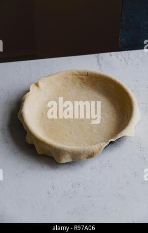 Las materias crudas y corteza de tarta en un molde para hornear sobre fondo de hormigón Imagen De Stock