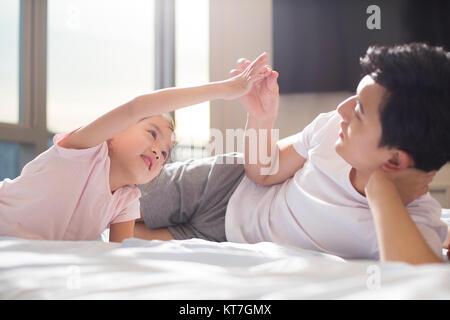 Alegre padre joven jugando con su hija en la cama Imagen De Stock