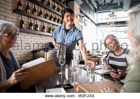 Amable camarera sirviendo a mujeres mayores amigos en restaurante. Imagen De Stock
