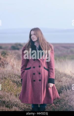 Una joven en un abrigo de lectura está de pie en el brezo en invierno Imagen De Stock