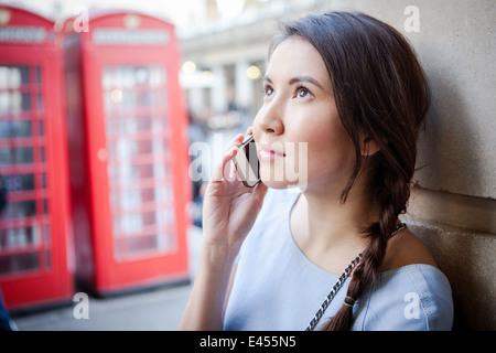 Mujer joven en smartphone, delante del cuadro de teléfonos rojos de Londres Imagen De Stock
