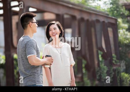 Alegres jóvenes amigos hablando al aire libre Imagen De Stock