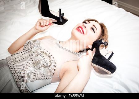 Feliz joven en vestido de noche, sosteniendo los zapatos en la cama Imagen De Stock