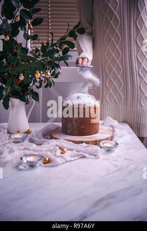 Mujer dusting Panettone pastel de Navidad con azúcar glas Imagen De Stock