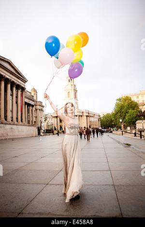 Mujer joven en vestido de noche sosteniendo globos, Trafalgar Square, Londres, Reino Unido. Imagen De Stock
