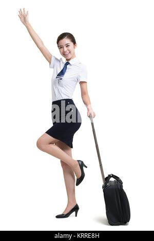 Sonriente azafata de aerolíneas con el saludo de equipaje con ruedas Imagen De Stock