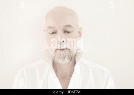 Triste y pensativo hombre viejo mirando hacia abajo. Él viste una camiseta unbuttoned blanco. Retrato de adultos Imagen De Stock
