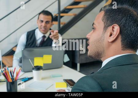 El joven es una conversación de negocios con sus colegas en la oficina. Formación empresarial. Imagen De Stock