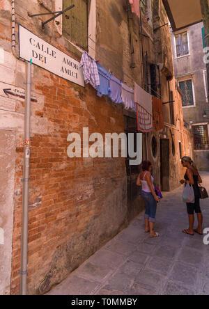 Las mujeres Italain charlando en una estrecha calle del casco antiguo de la ciudad, de la región del Veneto, Venecia, Italia Imagen De Stock