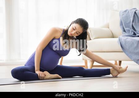 Alegre mujer embarazada practicando yoga en casa Imagen De Stock