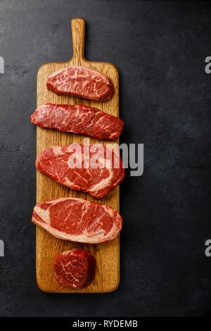 Variedad de materias Black Angus Prime filetes de carne de la hoja superior, Denver, Rib Eye, Lomo, filete de lomo Mignon sobre tablero de madera sobre fondo oscuro Imagen De Stock