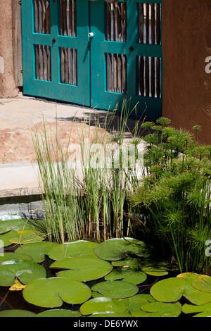 Estanque con nenúfares en el suroeste de los Estados Unidos de adobe en casa patio. Imagen De Stock