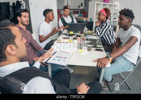 Jóvenes prometedores chicos discutir proyectos innovadores en la oficina. Imagen De Stock