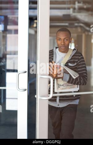 Varón de 18 años de estudiante universitario la apertura de una puerta después de salir de clase. Imagen De Stock