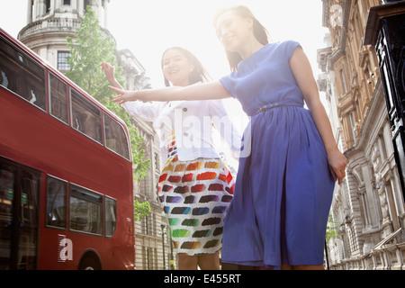 Dos jóvenes mujeres de pie en la calle de Londres, agitando a bus stop Imagen De Stock