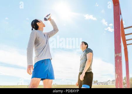 Los corredores macho descansando, agua potable en sunny park Imagen De Stock
