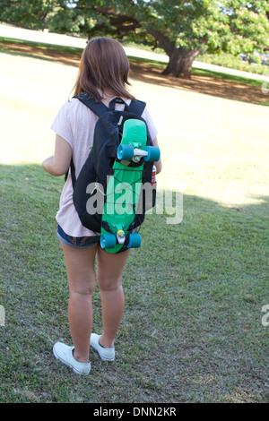 Monopatín atado a la mochila bolso mujer teen adolescente skater portable usando el transporte de moda de tendencia al aire libre chica senderismo Imagen De Stock