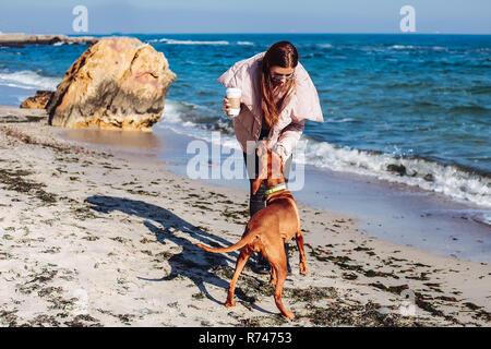 Mitad mujer adulta, sobre la playa de acariciar a su perro, Odessa, Odeska Oblast, Ucrania Imagen De Stock