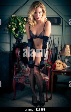 Un joven, atractivo, sexy mujer rubia plantea provocativamente y seductoramente vistiendo medias panty y bra negro Imagen De Stock