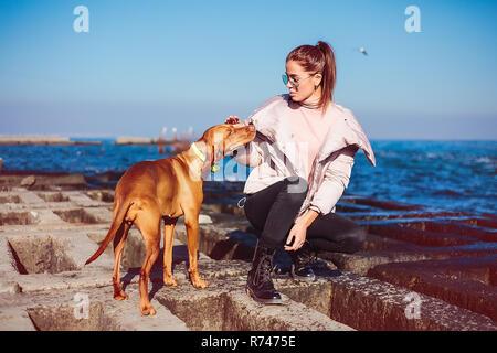 Elegante mujer adulta media agazapados en defensa del mar acariciar a su perro, Odessa, Odeska Oblast, Ucrania Imagen De Stock
