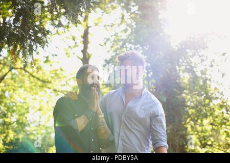 Afectuosa pareja homosexual masculina en sunny park Imagen De Stock