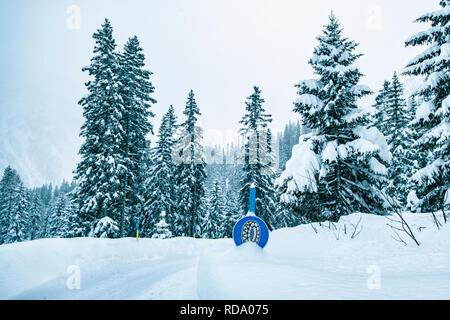 La nieve cubrió la calle signo con cadenas para la nieve. Imagen De Stock