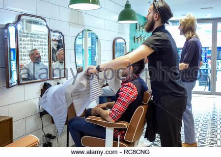 Los peluqueros corte de cabello del cliente. Imagen De Stock