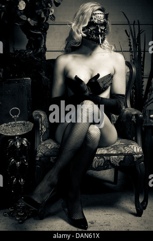 Imagen en blanco y negro de mujer vistiendo bauta máscara veneciana y cubriendo los pechos con las manos. Imagen De Stock