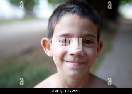 Primer plano de un niño hispano de pie en su barrio al anochecer. Imagen De Stock