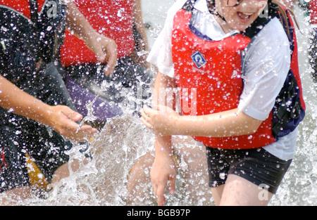Fotografía de la actividad de los niños jugando en el agua de mar escuela de vela Imagen De Stock