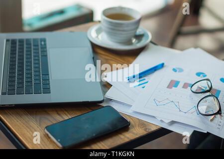 Escritorio, gafas, cafetera, teléfono, gráficos. Imagen De Stock
