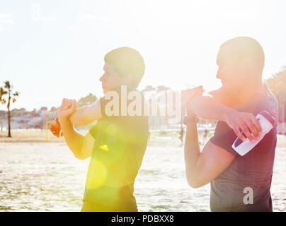 Los corredores masculinos brazos estiramiento en sunny beach Imagen De Stock