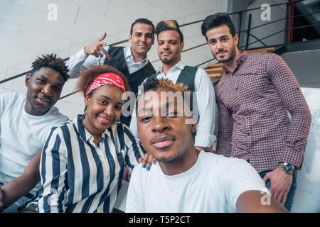 Jóvenes de diferentes nacionalidades tomar selfies en la habitación. La amistad de los pueblos. Imagen De Stock