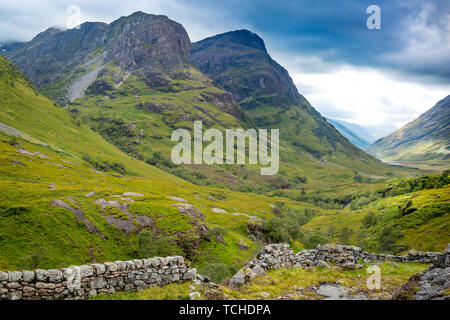 Muro de piedra y vistas al valle debajo de las montañas de Glencoe, Lochaber, HIghlands, Escocia Imagen De Stock