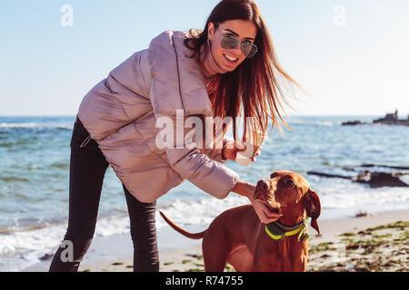 A mediados elegante mujer adulta, sobre la playa de acariciar a su perro, retrato, Odessa, Odeska Oblast, Ucrania Imagen De Stock