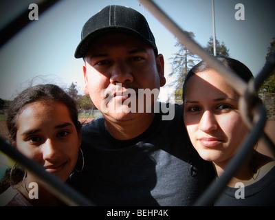 Padre de dos hijas mirando a través de la valla de béisbol Imagen De Stock