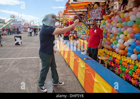 Hombre vestido con máscara de paloma apunta dart en globos, New Mexico State Fair. Imagen De Stock