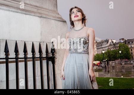 Modelo femenino en el vestido de noche al anochecer, Trafalgar Square, Londres, Reino Unido. Imagen De Stock