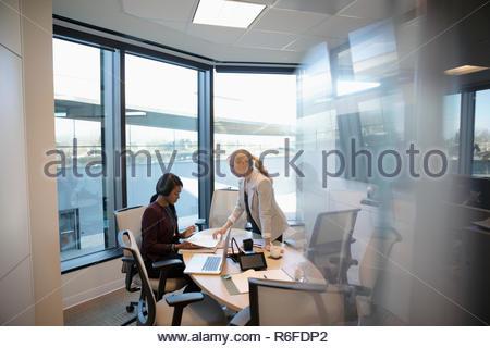 Empresarias revisando el papeleo en la sala reunión Imagen De Stock