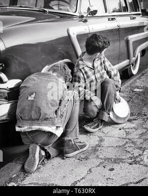1950 dos chicos en ropa desigual robando tapacubos de coche aparcado en la calle UN NIÑO ACTUANDO COMO LOOKOUT - w1763 HAR001 HARS AUTOMOBILE varones de riesgo ADOLESCENTE SNEAKERS LADRÓN DENIM ROBANDO B&W LADRÓN ROBO AVENTURA AUTOS Station Wagon conexión de robo de automóviles Vehículos adolescente felonía ilegal pre-adolescentes menores de edad pre-teen BOY COMPAÑERISMO EN BLANCO Y NEGRO la etnia CAUCÁSICA HAR001 Old Fashioned ROBO Imagen De Stock