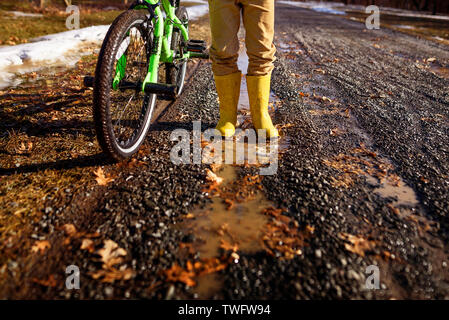 Close-up de un niño usando botas Wellington de pie junto a su bicicleta, Estados Unidos Imagen De Stock