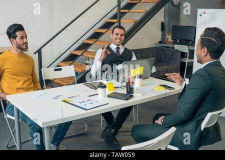 Encuentro de Negocios de jóvenes empresarios que están hablando en una mesa en la oficina. Imagen De Stock